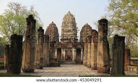 View of ruined columns in an ancient Buddhist temple, Wat Si Sawai, with three pagodas of Cambodian (Khmer) Style in background ~ Scenery of a ruined temple in Sukhothai Historical Park, Thailand - stock photo