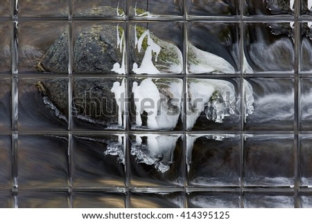 View of running water of small mountain creek and ice on the rocks, through window panes