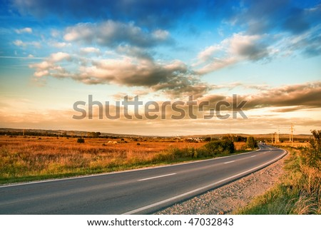 View of rural road and blue cloudy sky - stock photo