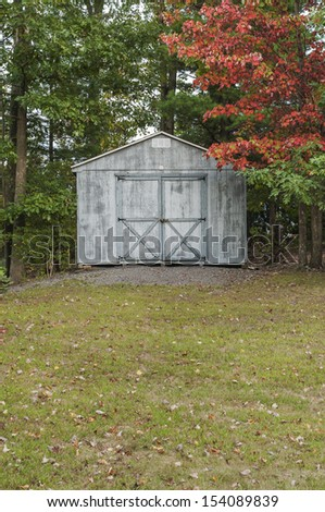 View of rural shed in early autumn, with red foliage and fallen leaves on the lawn.