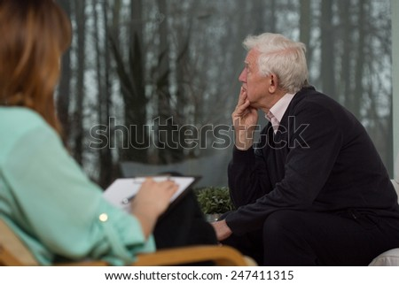 View of sad man talking with psychologist - stock photo