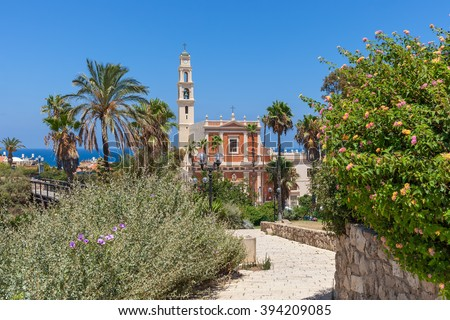 View of Saint Peter's church among trees, palms and bushes under blue sky in old Jaffa, Israel.