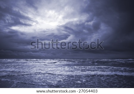 View of sea and light hole in clouds few minutes before storm. Blue tone. - stock photo