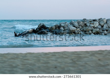 view of sea and sand beach with stones at sunset in the evening, sea tide, natural photo, Bibione, Italy - stock photo