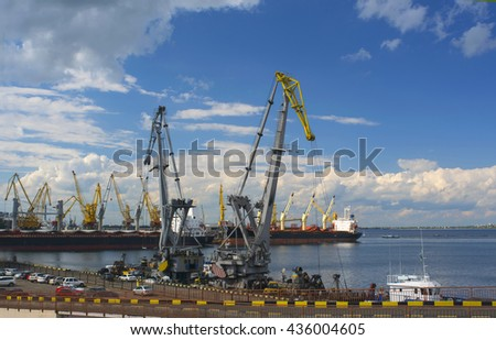 View of seaport with cranes on daylight cloudy sky background