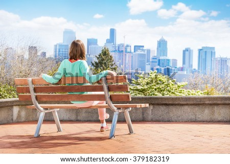 View of Seattle downtown woman on bench in park - stock photo