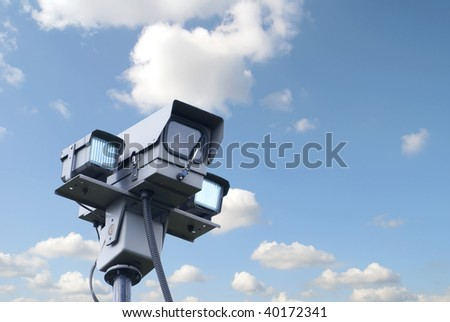 View of security camera against blue cloudy sky - stock photo