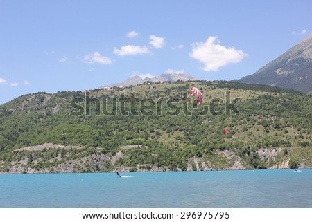 View of Serre Ponçon lake between Embrun and Savines le Lac. Serre Ponçon lake is famous for its kitesurfing spots. Hautes Alpes, Ecrins, Alps, France. - stock photo