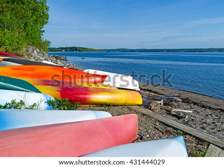 View of several canoes, kayaks and dinghies stored on a beach at Northport Maine in the early morning light. - stock photo