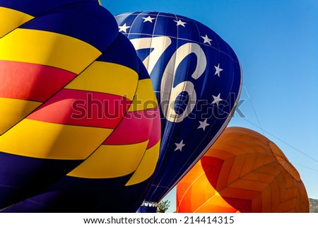 View of several hot air balloons getting inflated before take off at balloon festival - stock photo