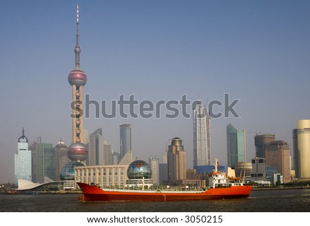 View of Shanghai with the Oriental Pearl Tower and a red ship in the foreground - stock photo