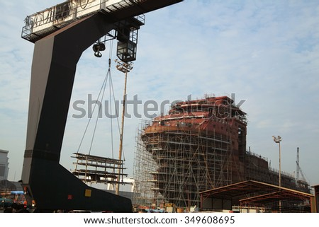 View of shipyard with straddle crane and ship under construction - stock photo