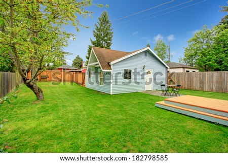 View of siding house with fenced backyard, View of green lawn, small concrete floor patio area with table set - stock photo