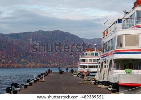 View of sightseeing boats parking by the pier & mountains of colorful autumn foliage in the background by the beautiful Lake Towada in fall season, in Towada Hachimantai National Park, Aomori, Japan