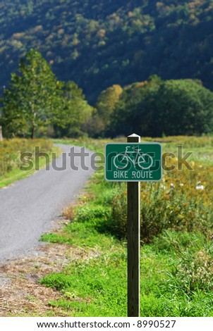 View of sign marking  bike route, with bike trail and countryside in background.