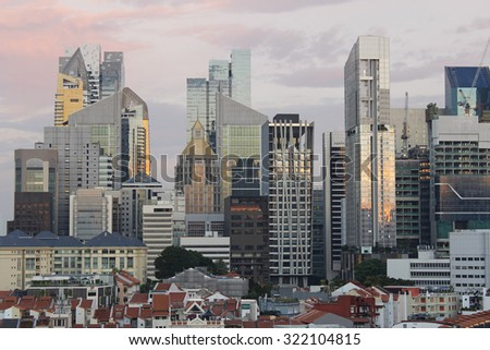 View of Singapore's Chinatown with red rooftop of shop houses and city's financial district and skyscrapers as background in sunset  - stock photo
