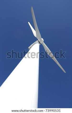 View of single windmill generating electricity against blue sky - stock photo