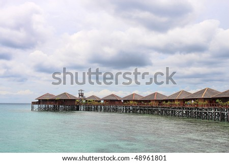 View of Sipdan water village resort at Mabul Island under cloudy day.