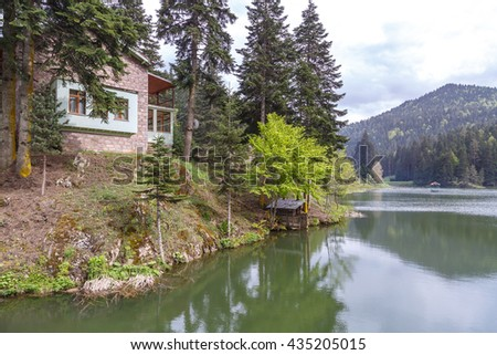 View of small Akgol lake in Ayancik, Sinop around big mountains with high pine trees on cloudy sky background.