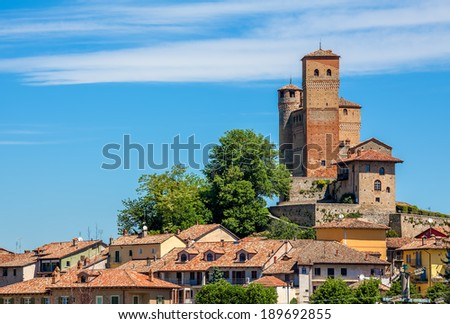 View of small italian town under blue sky in Piedmont, Northern Italy. - stock photo