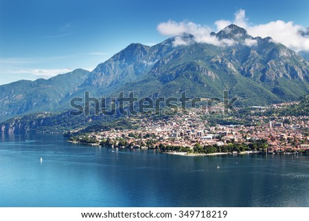 View of small town at the foot of Alpine mountain, Mandello del Lario, Como lake Italy. - stock photo
