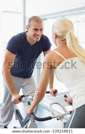 View of smiling fit couple working on exercise bikes at the gym