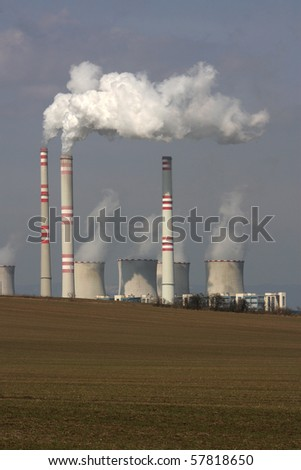 view of smoking power plant over the field - stock photo