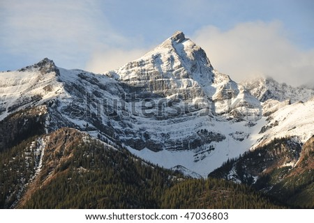 View of snow rocky mountains and forests in early september at chester lake area, kananaskis country, alberta, canada - stock photo