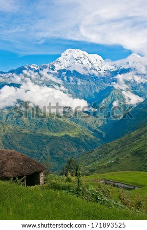 View of snowed mountain peak above the green valley in Himalayas, Nepal - stock photo