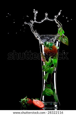 View of soft drink splashing out of glass on black back - stock photo