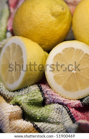 View of some yellow lemons sliced on top of table cloth.