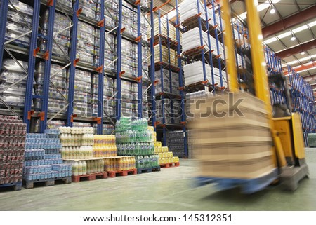 View of speeding forklift in warehouse - stock photo