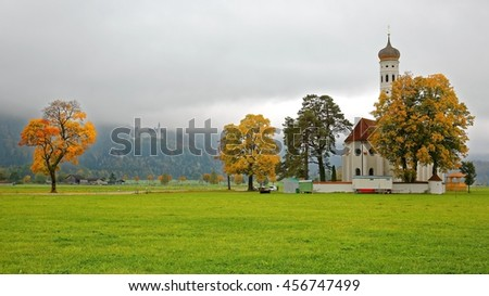 View of St. Coloman Church & beautiful autumn trees in the meadow on a misty morning with New Swanstone Castle ( Schloss Neuschwanstein ) on mountaintop in the background in Schwangau, Fussen Germany  - stock photo