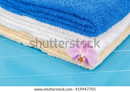 View of  stack of towels on a blue wooden background.