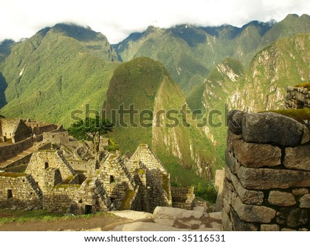 View of stone buildings and mountains at the ancient Inca city of Machu Picchu, Peru. - stock photo