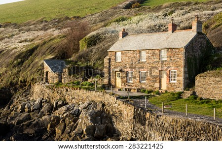 View of stone cottage and hillside in late evening sunlight in Port Quin, Cornwall, England, UK - stock photo