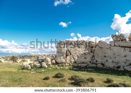 View of stone structures of ancient Ggantija Temples in Gozo Malta, on cloudy blue sky background. - stock photo