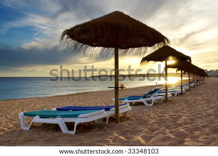 View of straw sunshades, and blue deck-chairs in a beach at sunset - stock photo