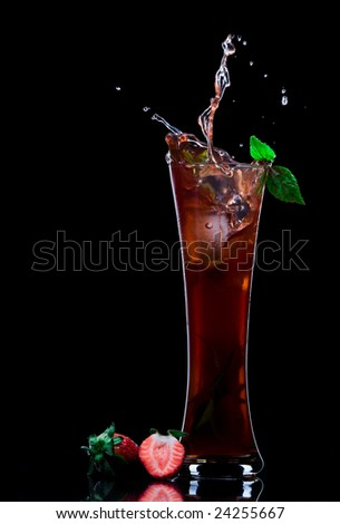 View of strawberry juice splashing out of glass on black back