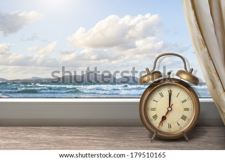 View of summer sea under blue sky from window with alarm clock - stock photo