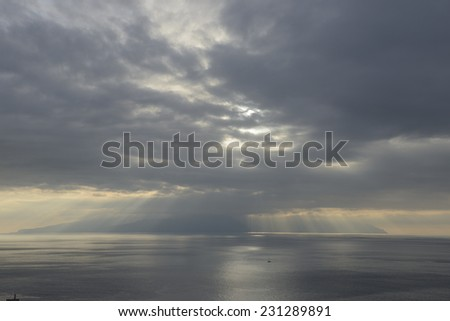 View of sunrays through the clouds over La Gomera Island from Los Gigantes, Tenerife, Canary Islands, Spain. - stock photo