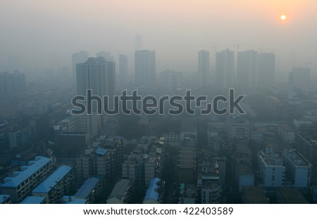 View of sunrise through the smog in a modern Chinese city - stock photo