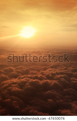 View of sunset above clouds from airplane window - stock photo