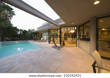 View of swimming pool and illuminated modern home exterior - stock photo