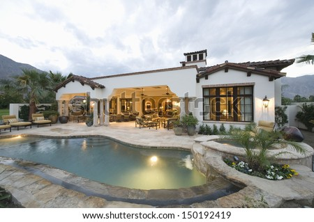 View of swimming pool and modern home exterior - stock photo