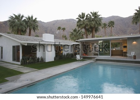 View of swimming pool and modern home exterior against mountains - stock photo