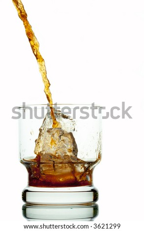 view of table glass with ice in it getting filled with soft drink - stock photo