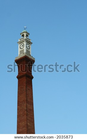 view of tall clock tower against blue sky, enough space for editing, easy to crop