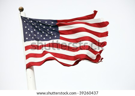 View of tattered American flag on flagpole blowing in the wind. - stock photo