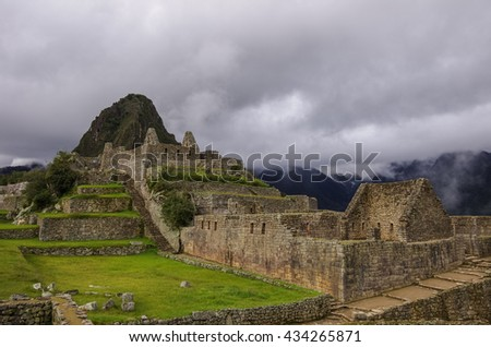View of temple ruins in Lost Inca City of Machu Picchu. Low clouds. Cusco Region,Sacred Valley, Peru - stock photo